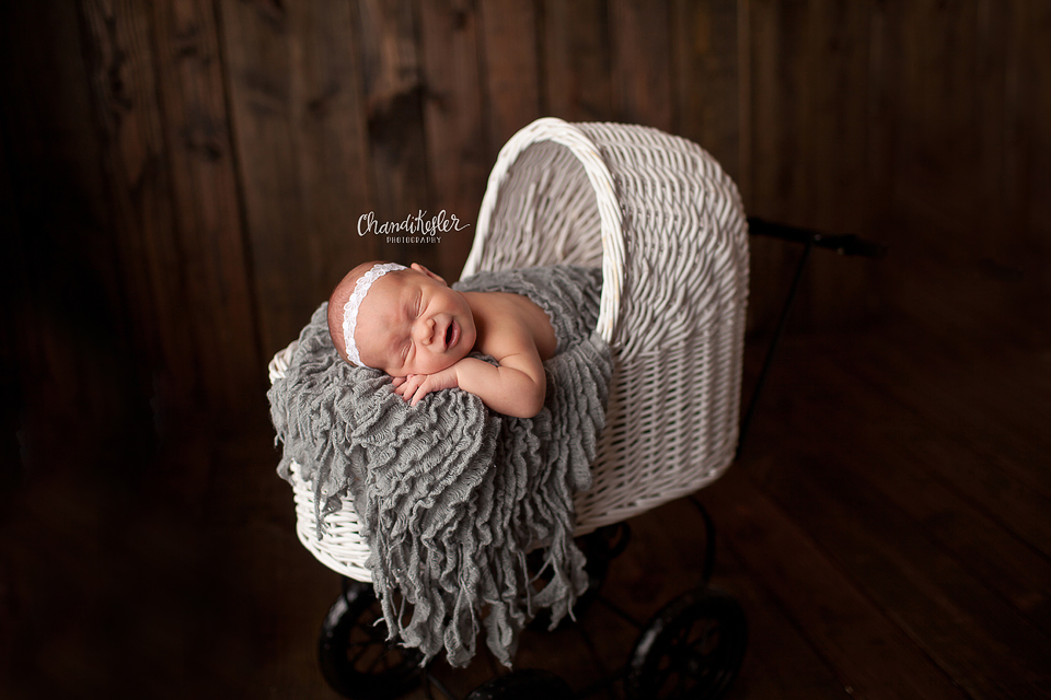 Mackinaw Newbron Photographer - newborn in prop posing